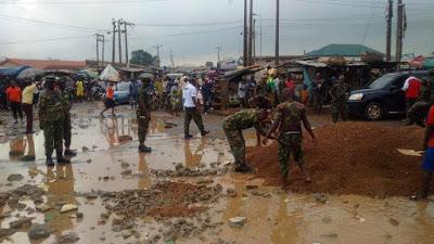 Nigerian Soldiers clear gutter, fix potholes in Ikorodu