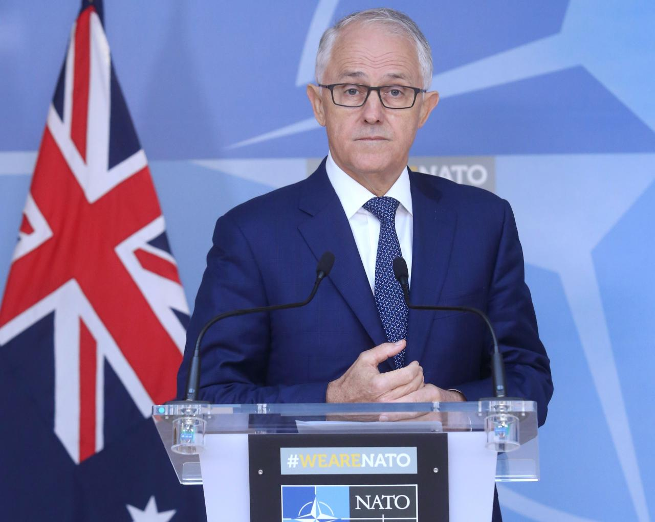 Australian PM, fighting for political life, dumps tax policy