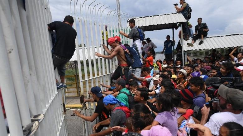 Migrants gather at border bridge to Mexico on trek to U.S.